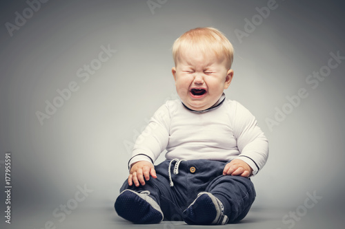 Crying baby sitting on the ground. Fotobehang