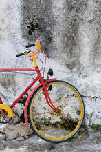 Bright Red And Yellow Bicycle Standing Beside A Rustic Wall