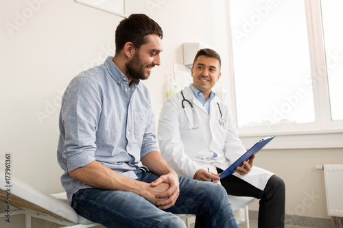 Fototapeta smiling doctor and young man meeting at hospital