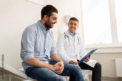 Fényképezés smiling doctor and young man meeting at hospital