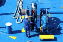 Man Working On Windlass Of Passenger Ship.