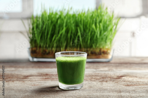 Obraz Shot of wheat grass juice on wooden table - fototapety do salonu