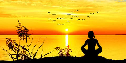 mujer haciendo yoga bajo la puesta de sol