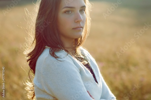Portrait of brunette girl on the meadow in contra light
