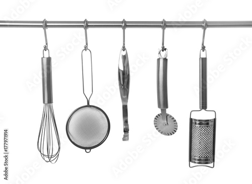 Set Of Cooking Utensils Hanging On Rack Isolated White