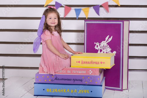Baby doll girl in pink dress with pout lips and brunnette hair posing with huge awesome books different colours about prodigy maracle wonderland Poster