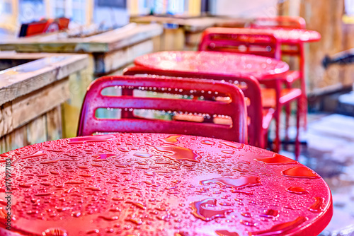 Fotografía Wet red table, chairs closeup outside restaurant sitting area by sidewalk during