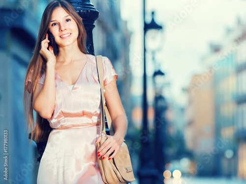 Poster Gypsy happy woman talking on phone and standing in old town