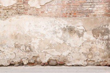 Old weathered vintage brick wall with broken plaster and pavement on the ground. Grungy urban background.