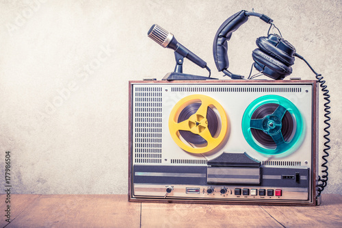 Fotografía  Retro reel to reel tape recorder, microphone and headphones on wooden table front concrete wall background
