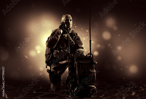 Photo  The soldier of the special unit in military uniform sits near the satellite communications apparatus and causes support
