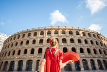 Woman In Red Dress With Spanish Hand Fan Stnading Back In Front Of The Bullring Amphitheatre In Valencia City, Spain