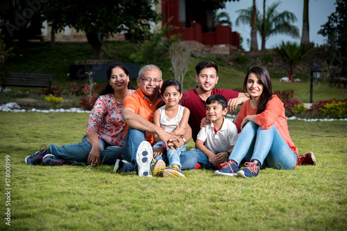 closeup photograph of Indian extended family sitting outdoors smiling Wallpaper Mural