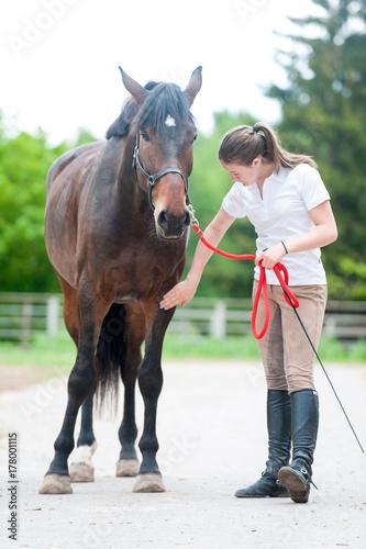 Obraz na plátně Teenage equestrian girl checking for injury of bay horse leg