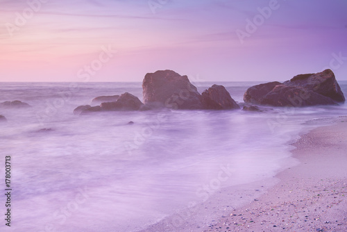 Tuinposter Purper Summer seasonal natural vacation background. Romantic morning at sea. Big boulders sticking out from smooth wavy sea. Pink horizon with first hot sun rays. Long exposure.