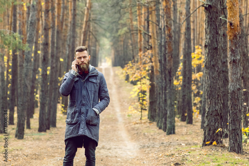 Photo Stands Roe bearded frowning hipster in the forest talking on the phone