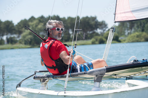 Spoed Foto op Canvas Water Motor sporten man sitting on a sailboat