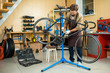 Young handsome mechanic wearing apron repairing bicycle while listening to music in headphones, interior of modern workshop on background