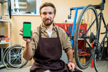 Portrait Of Smiling Bearded Mechanic Sitting On Haunches And Showing Smartphone With Blank Screen To Camera, Interior Of Modern Bicycle Repair Shop On Background