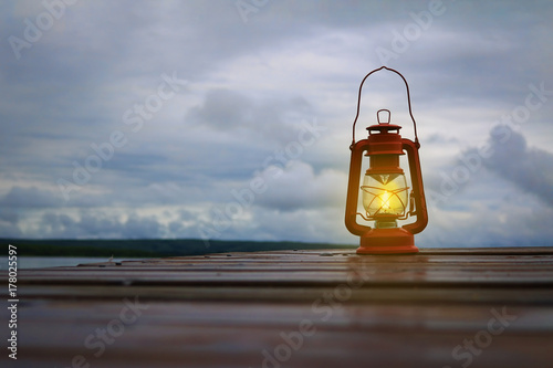 Burning lantern on a dock at a lake in the twilight Canvas Print