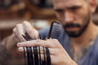 Close up of a hairdresser cutting hairs between his fingers