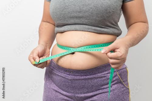 Plakat Z nadwagą kobieta sprawdza out jego ciało sadło z zieloną pomiarową taśmą dla otyłości na szarym tle, Zdrowy pojęcie