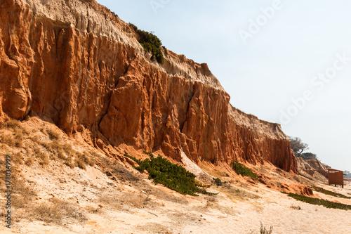 Fototapeta Czerwone gliniane falezy obok plaży