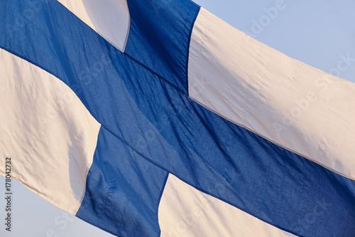 Plakat Fińska flaga pod niebieskim niebem. Symbol Finlandii. Europa.