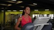 Close up of attractive mixed race woman running on the treadmill in the sport gym in slow motion.