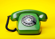 Old Green Telephone On A Yellow Background