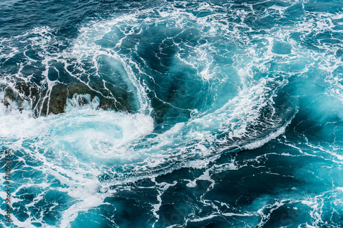 vertiginous, swirling foamy water waves at the ocean photographed from above Wallpaper Mural