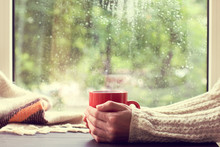 Cozy Home Atmosphere In Autumn/ Red Mug Of Hot Drink In Hand, When Behind Is Window Is Rain