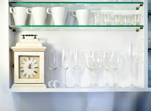 Tidy And Neat White Cupboard With Glasses And Vintage Clock In Restaurant