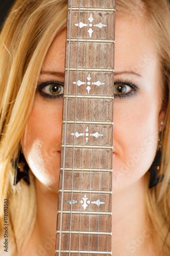 Plakat Blondynki kobieta trzyma gitarę elektryczną, czarny tło