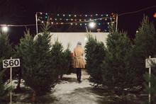 A Woman Walking Through A Christmas Tree Lot