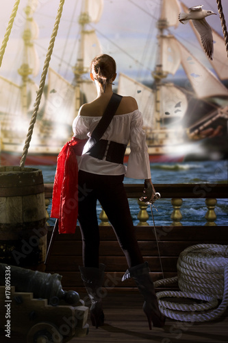 Cuadros en Lienzo pirate captain in sexy clothes calmly stands on the deck of her ship under enemy