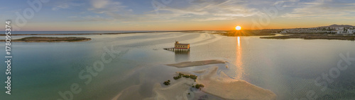 Photo Aerial sunset panoramic and historic life-guard building at Fuseta fishing town, in Ria Formosa wetlands nature conservation park, Algarve
