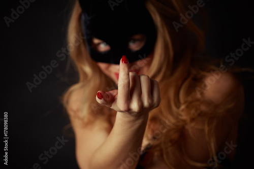 Photo  A beautiful woman with a mask on her face makes a beckoning gesture with her finger