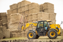 Yellow Tractor Stacks Bales Of Hay On The Field