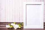 blank photo frame with copyspace and white rose flowers on wooden background. greeting card .
