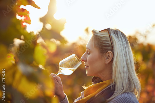 Fotografía Portrait of a woman tasting white wine in autumn colorful vineyard