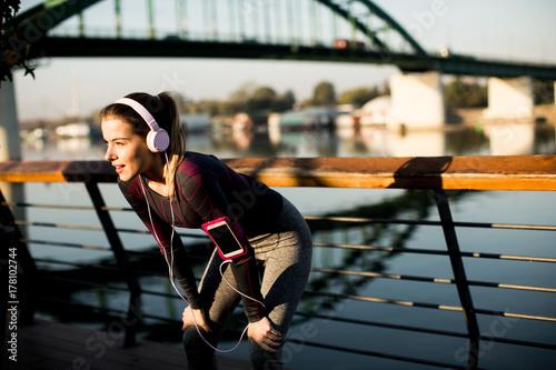 Plakat Młoda kobieta ćwiczenia na deptaku po uruchomieniu