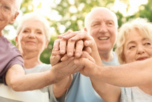 Group Of Elderly People Putting Hands Together As Symbol Of Unity