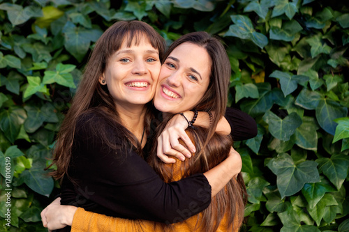 Outdoor portrait of two happy sisters in a park Canvas-taulu