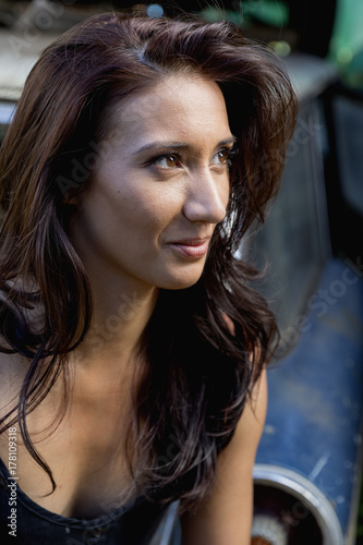 Young mixed race woman sitting on tailgate of wrecked classic ca Poster