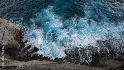 Wall Murals Air photo Aerial view to ocean waves and rock coast