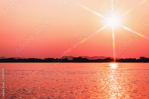 Papiers peints Corail Amazing sunset at Paraguai river in Pantanal, Brazil. The river and the sun with flares at a golden hour sunset, water reflection and silhouette of nature on background.