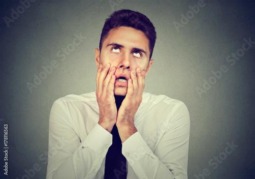 Valokuva  Desperate business man isolated on gray background