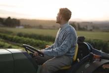 Farmer Driving Tractor In Field