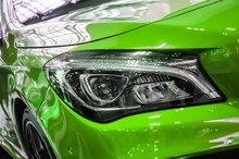The Headlamp Of A Green Sports Car Of Aggressive Form With A Part Of The Hood And Black Wheel, Bumper And Partronik